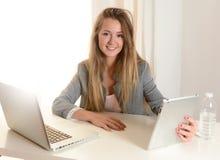 Mulher de negócio nova que trabalha em seu portátil Fotos de Stock