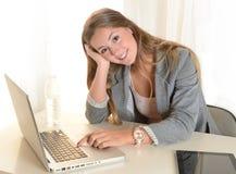 Mulher de negócio nova que trabalha em seu portátil Imagem de Stock