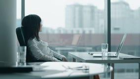 Mulher de negócio nova que trabalha em um portátil no escritório moderno que sorri e toma uma ruptura video estoque