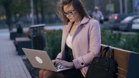 Mulher de negócio nova que trabalha no laptop no banco no quadrado de cidade video estoque