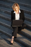 Mulher de negócio nova que usa o portátil nas etapas Imagem de Stock Royalty Free