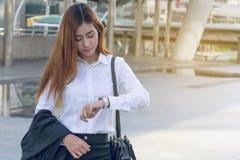 Mulher de negócio nova que verifica o tempo em seu relógio foto de stock royalty free