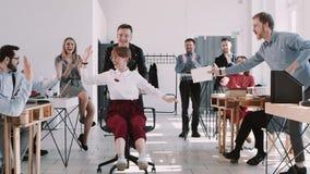 A mulher de negócio nova de sorriso VERMELHA de EPIC-W comemora o sucesso com os colegas de escritório felizes que montam o movim video estoque