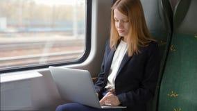 A mulher de negócio nova vai pelo trem, trabalha em um portátil e olha a janela vídeos de arquivo