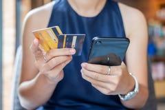 Mulher de negócio ocasional nova que guarda o cartão de crédito e que usa o smartphone do écran sensível para a compra em linha a foto de stock royalty free