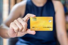 Mulher de negócio ocasional nova que guarda o cartão de crédito para a compra em linha ao fazer ordens no café negócio, estilo de imagens de stock