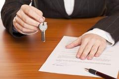 A mulher de negócio prende a chave e o contrato nas mãos Fotografia de Stock Royalty Free