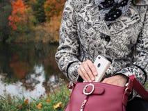 A mulher de negócio puxa um telefone celular do saco A mulher toma o telefone celular fora da bolsa fotografia de stock