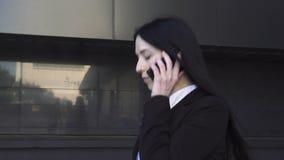 Mulher de negócio que anda e que fala no telefone video estoque