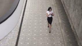 Mulher de negócio que anda e que usa um smartphone video estoque