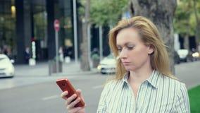 Mulher de negócio que anda no negócio do centro, falando no telefone, movimento lento, 4k video estoque