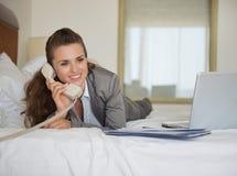 Mulher de negócio que coloca na cama com portátil Imagens de Stock