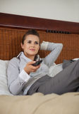 Mulher de negócio que coloca na cama e na tevê de observação Imagem de Stock