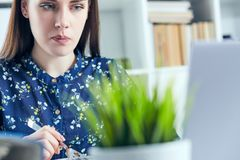 Mulher de negócio que come o almoço em seu local de trabalho que olha a tela do portátil Dobradores com originais no primeiro pla Imagem de Stock