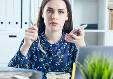 Mulher de negócio que come o almoço em seu local de trabalho que olha a tela do portátil Dobradores com originais no primeiro pla Fotos de Stock