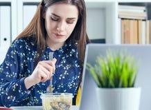 Mulher de negócio que come o almoço em seu local de trabalho que olha a tela do portátil Dobradores com originais no primeiro pla Fotos de Stock Royalty Free