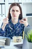 Mulher de negócio que come o almoço em seu local de trabalho que olha a tela do portátil Dobradores com originais no primeiro pla Fotografia de Stock Royalty Free