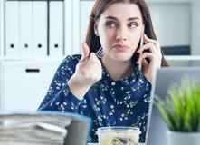 Mulher de negócio que come o almoço em seu local de trabalho que olha a tela do portátil Dobradores com originais no primeiro pla Foto de Stock Royalty Free