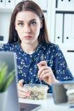 Mulher de negócio que come o almoço em seu local de trabalho que olha a tela do portátil Dobradores com originais no primeiro pla Foto de Stock