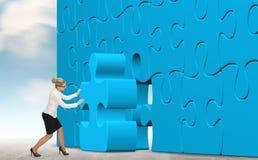 Mulher de negócio que constrói um enigma azul em um fundo do céu Fotografia de Stock