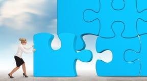 Mulher de negócio que constrói um enigma azul em um fundo do céu Imagem de Stock Royalty Free