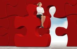 Mulher de negócio que constrói um enigma em um fundo do céu Imagem de Stock