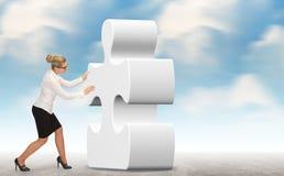 Mulher de negócio que constrói um enigma em um fundo do céu Foto de Stock