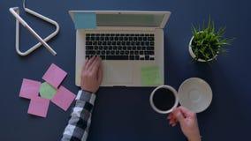 Mulher de negócio que datilografa em um portátil ao sentar-se na tabela e no café bebendo As etiquetas com ideias do negócio estã filme
