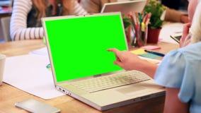 Mulher de negócio que datilografa no portátil durante a reunião video estoque