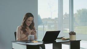 Mulher de negócio que enrola o móbil no lugar de trabalho Senhora de sorriso que tem a ruptura video estoque