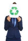 A mulher de negócio que esconde atrás recicl o sinal Fotografia de Stock