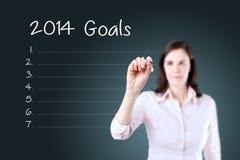 A mulher de negócio que escreve a placa 2014 objetivos alista o fundo azul Fotografia de Stock Royalty Free