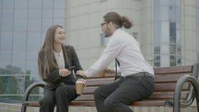 Mulher de negócio que escuta seu colega do homem de negócios no banco na frente da construção incorporada ao tentar sair - vídeos de arquivo