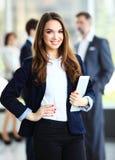 Mulher de negócio que está no primeiro plano com uma tabuleta em suas mãos Imagem de Stock Royalty Free