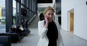 Mulher de negócio que fala no telefone video estoque