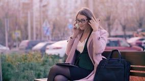 Mulher de negócio que fala no telefone celular e que usa a tabuleta no banco na cidade moderna video estoque