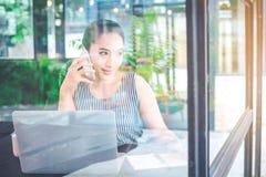 Mulher de negócio que fala no telefone e que escreve em uma almofada de nota dentro imagens de stock royalty free