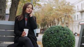 Mulher de negócio que fala no telefone e para beber o café no banco na rua filme