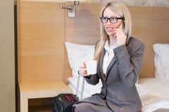 Mulher de negócio que fala no telefone na sala de hotel fotografia de stock