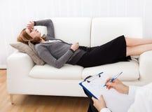 Mulher de negócio que fala a seu psiquiatra que explica algo Imagem de Stock
