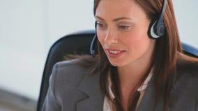 Mulher de negócio que fala sobre os auriculares vídeos de arquivo