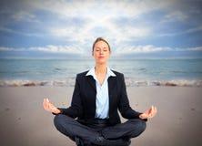 Mulher de negócio que faz a ioga na praia. Fotografia de Stock