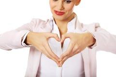 Mulher de negócio que faz uma forma do coração com suas mãos imagens de stock