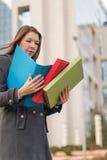 Mulher de negócio que guarda dobradores com originais fora Fotografia de Stock Royalty Free