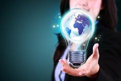 Mulher de negócio que guarda a lâmpada de no mundo inteiro Fotos de Stock