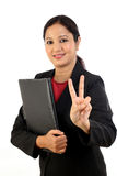 Mulher de negócio que guarda o dobrador e que faz o sinal da vitória Imagem de Stock Royalty Free