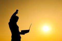 Mulher de negócio que guarda o portátil na silhueta do por do sol fotografia de stock