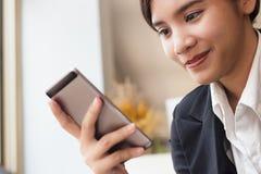 Mulher de negócio que guarda o smartphone em sua mão e que verifica o email imagem de stock royalty free