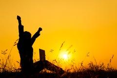 Mulher de negócio que guarda a silhueta do por do sol do portátil fotos de stock royalty free