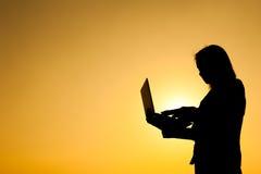 Mulher de negócio que guarda a silhueta do por do sol do portátil fotos de stock
